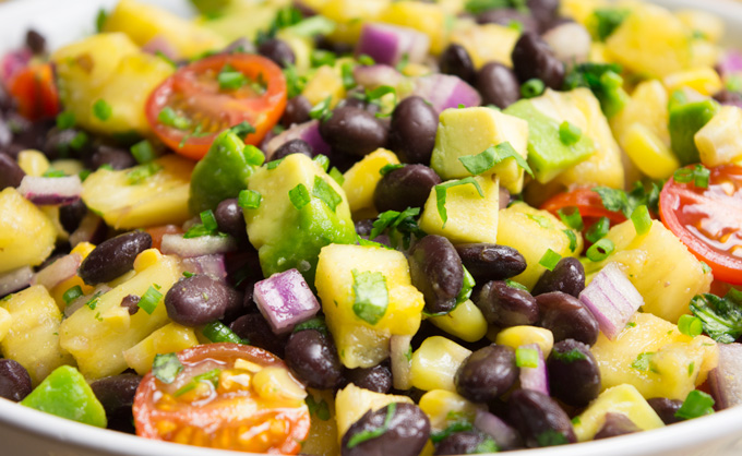 Pineapple Fiesta Salad close up. The salad consists of sweet pineapple, juicy tomatoes, diced avocado, red onion and black beans covered in a tangy lime dressing.