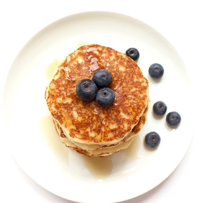 A top view of pancakes topped with fresh blueberries