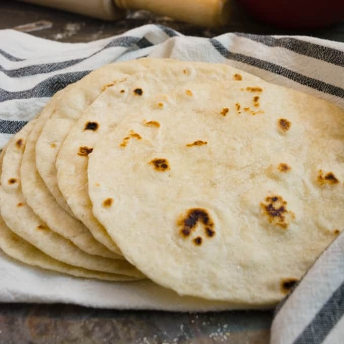 A stack of flour tortillas on a white with blue stripes towel.