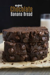 3 stacked slices of vegan Chocolate banana bread with a glass of almond milk.