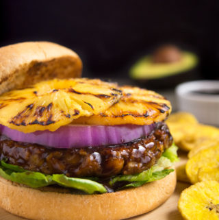 Grilled huli-huli vegan burger topped with red onion and grilled pineapple rings. Served with a side of plantains chips and extra sauce.