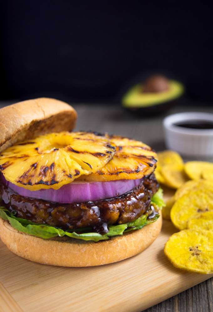 Grilled huli-huli vegan burger topped with red onion and grilled pineapple rings. It's served with a side of plantain chips.