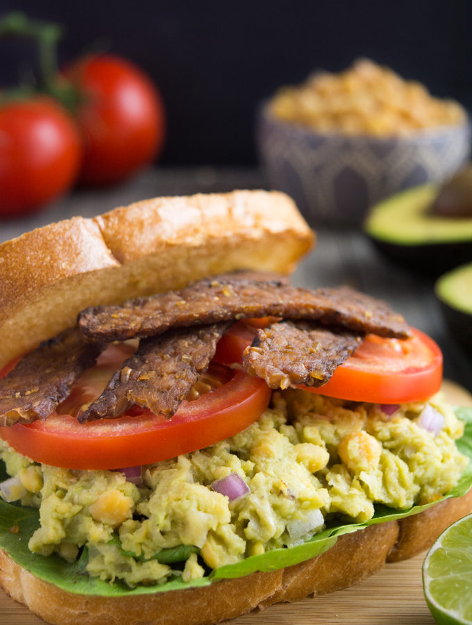 avocado chickpea BLT sandwich piled with lettuce, avocado chickpea mash, sliced tomato and tempeh bacon.