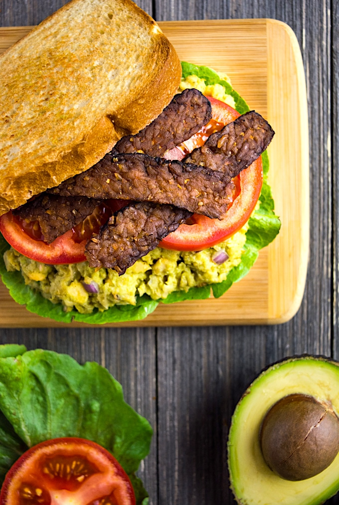 Vegan BLT sandwich with avocado chickpea mashed topped with tempeh bacon.