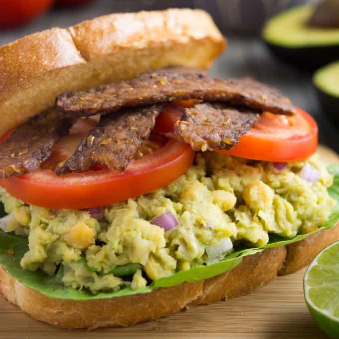 Avocado chickpea BLT sandwich on a wooden cutting board.
