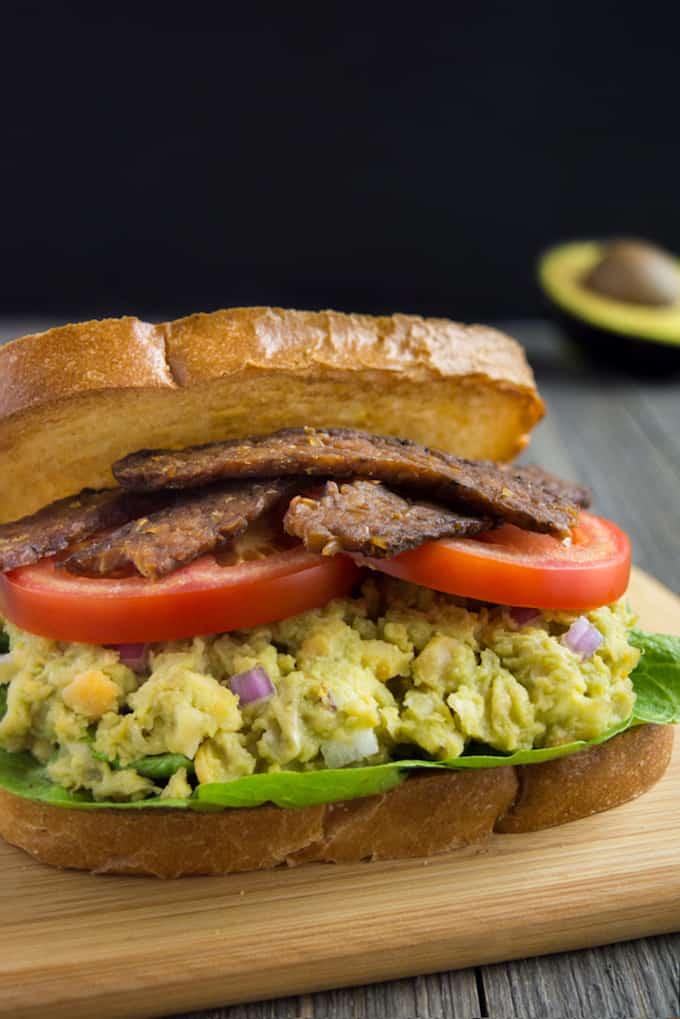 Avocado Chickpea BLT sandwich on a cutting board.