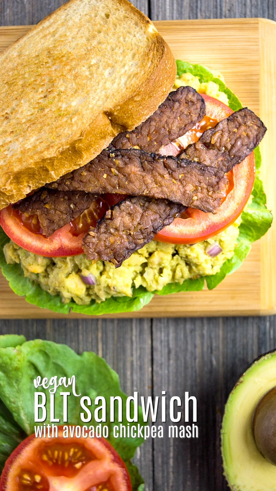vegan BLT sandwich with avocado chickpea mash, tempeh bacon, and tomato slices on a cutting board.