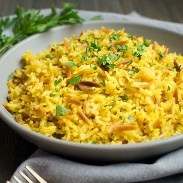 A gray bowl filled with rice pilaf topped with fresh chopped parsley.