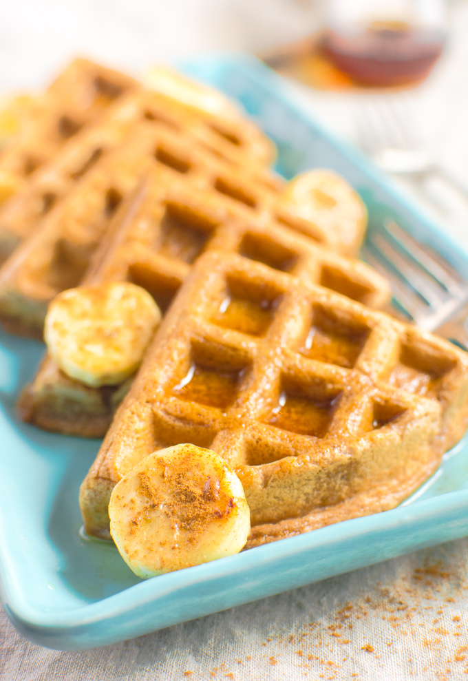 Cinnamon Vegan Waffle triangles topped with bananas and maple syrup.
