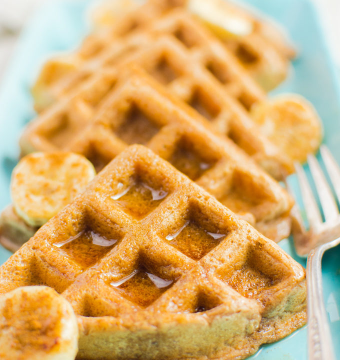 Cinnamon Vegan Waffles cut in triangles, topped with banana slices and drizzled with maple syrup.