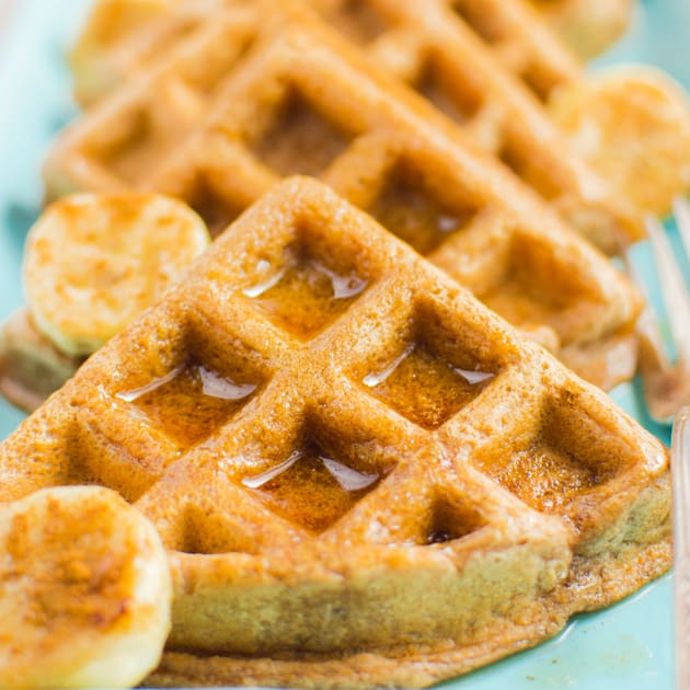 Vegan cinnamon waffle triangles topped with maple syrup on a rectangular turquoise plate.