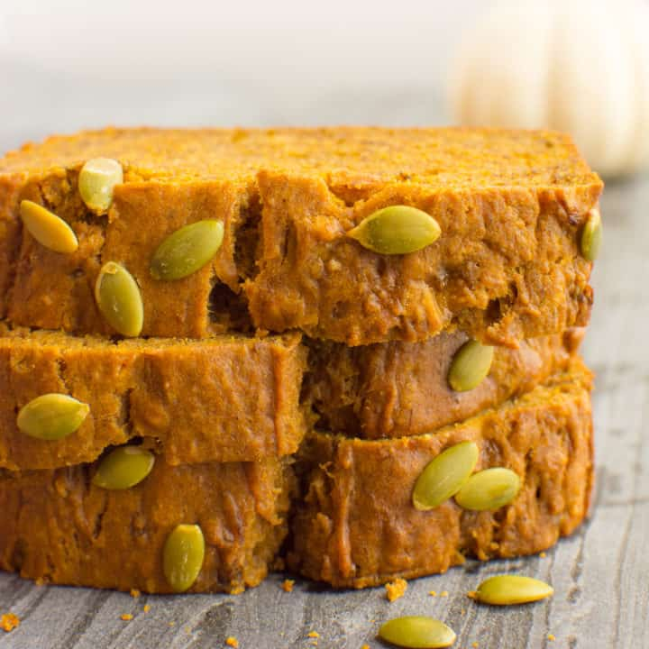 3 stacked slices of pumpkin bread topped with pumpkin seeds.