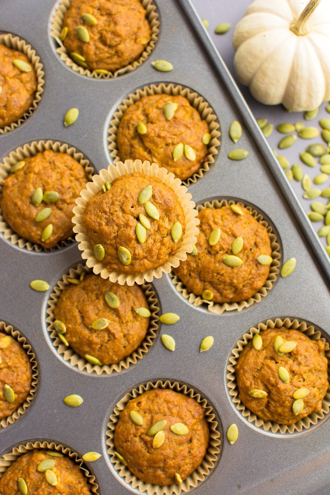 Vegan pumpkin banana bread muffins topped with pumpkin seeds and in a muffin tin.