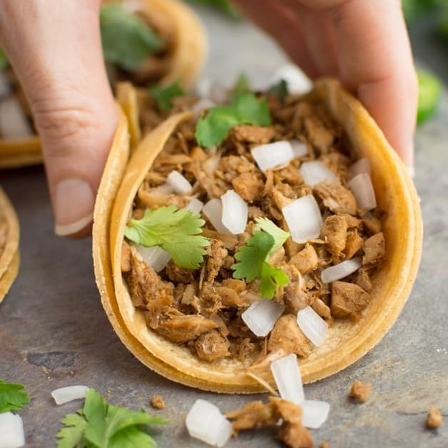 A hand picking up a jackfruit taco with fresh diced onion and cilantro in a corn tortilla.