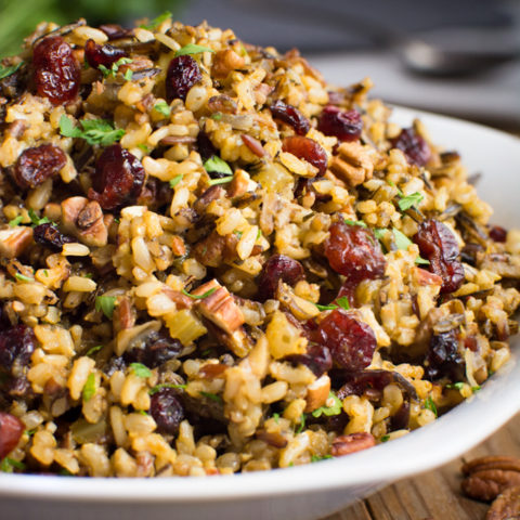 A serving bowl of wild rice stuffing with dried cranberries and toasted pecans.