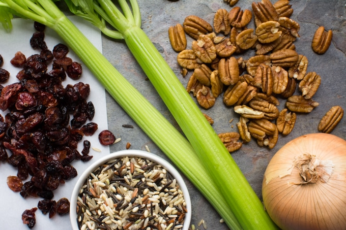Wild rice stuffing ingredients - celery stalks, wild rice, pecans, onion and dried cranberries.