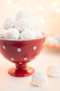 Vegan snowball cookies in a red holiday dish.