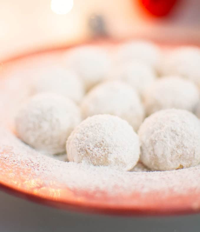 Vegan snowball cookies on a red serving plate.
