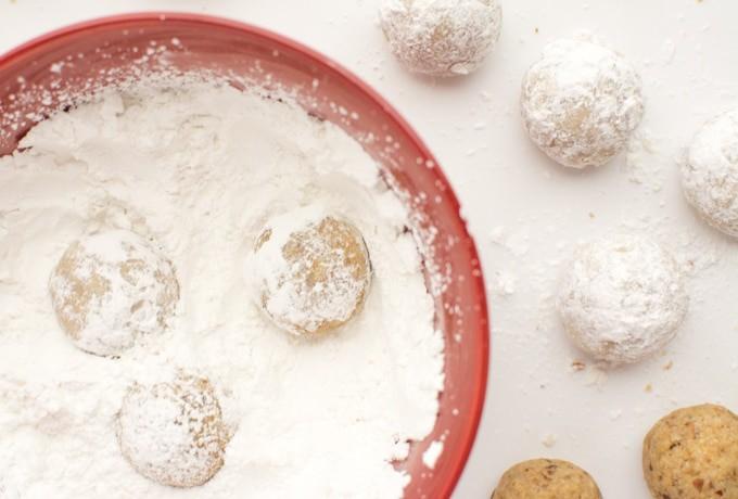Vegan snowball cookies being rolled in powdered sugar.
