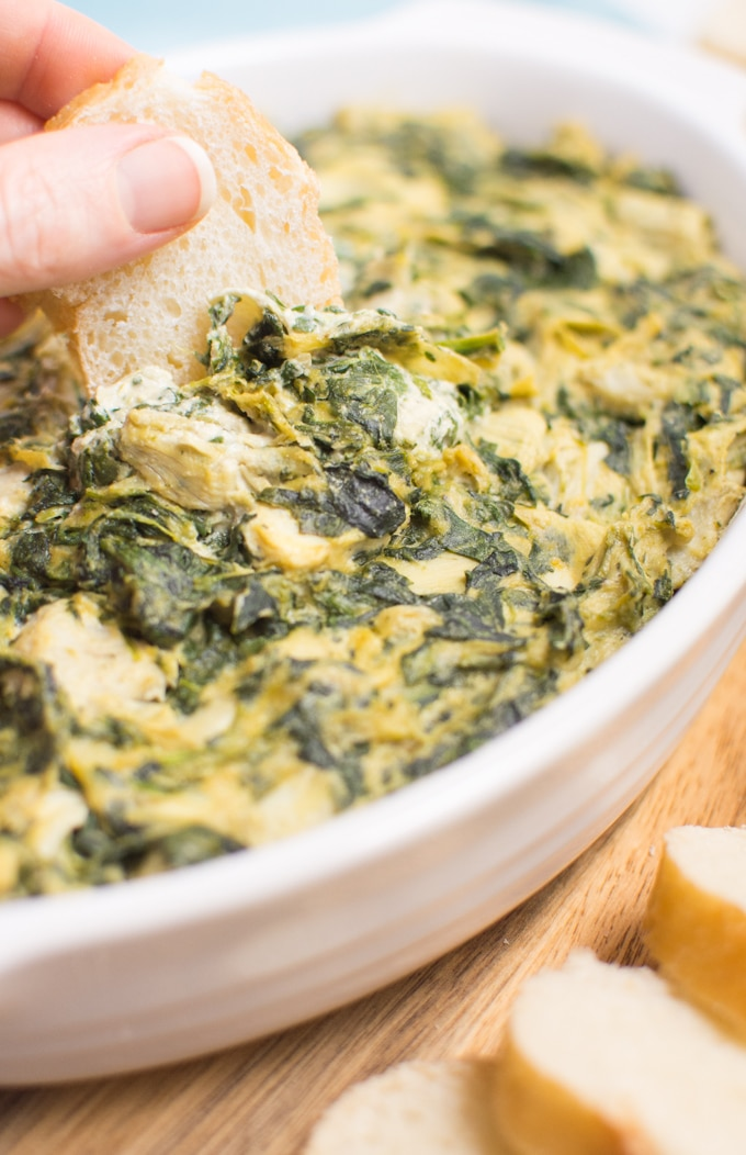 A slice of french bread being dipped into vegan spinach artichoke dip.