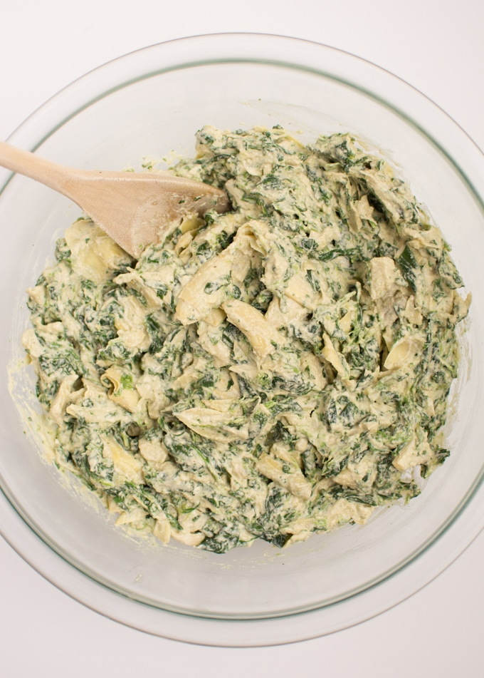 Mixing together the ingredients for vegan spinach artichoke dip