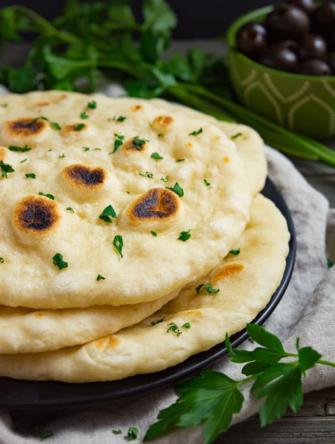 Soft vegan naan bread stacked on a plate.