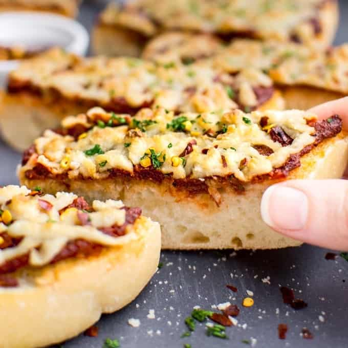 fingers grabbing a slice of french bread pizza topped with marinara and vegan cheese.