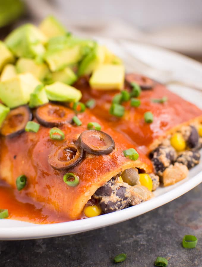 Two vegan black bean enchiladas on a white plate topped with extra sauce, green onions, sliced olives, and diced avocado.