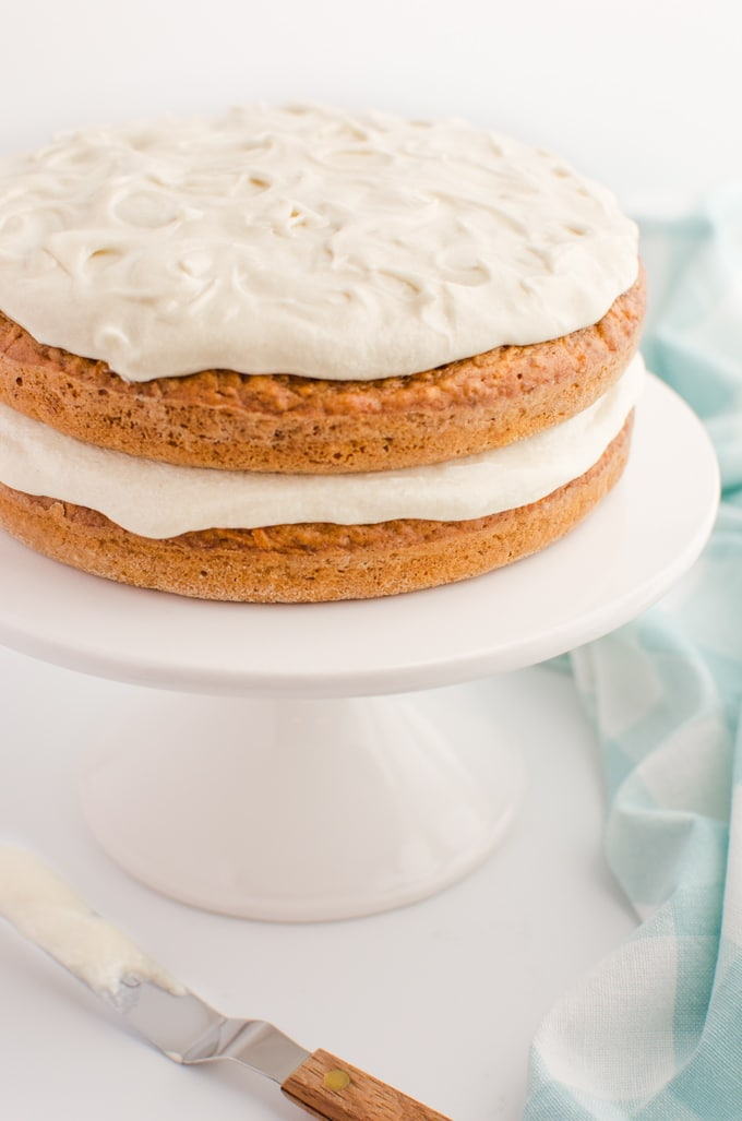 Two layer vegan carrot cake with cream cheese frosting on a white cake stand.