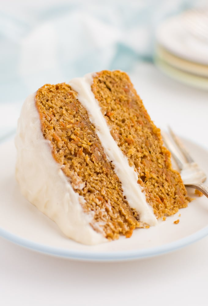 Carrot cake on a white plate with a fork.