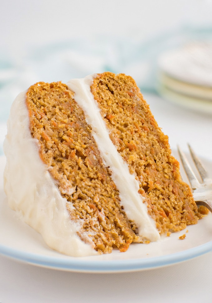 A slice of vegan carrot cake with cream cheese frosting on a white plate with a fork.
