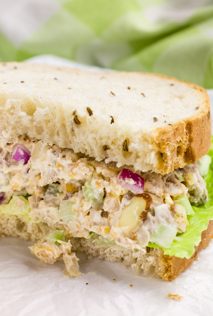 Vegan chicken salad on rye bread cut in half.