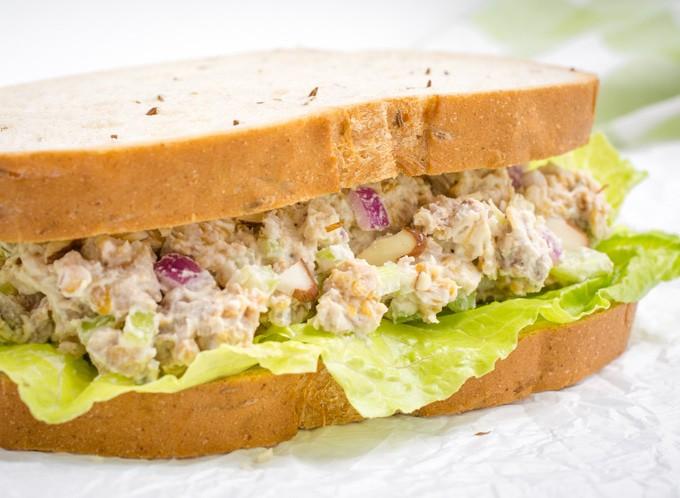 A vegan sandwich with jackfruit, chickpeas, mayo, almond slivers, onion, and celery on rye bread.