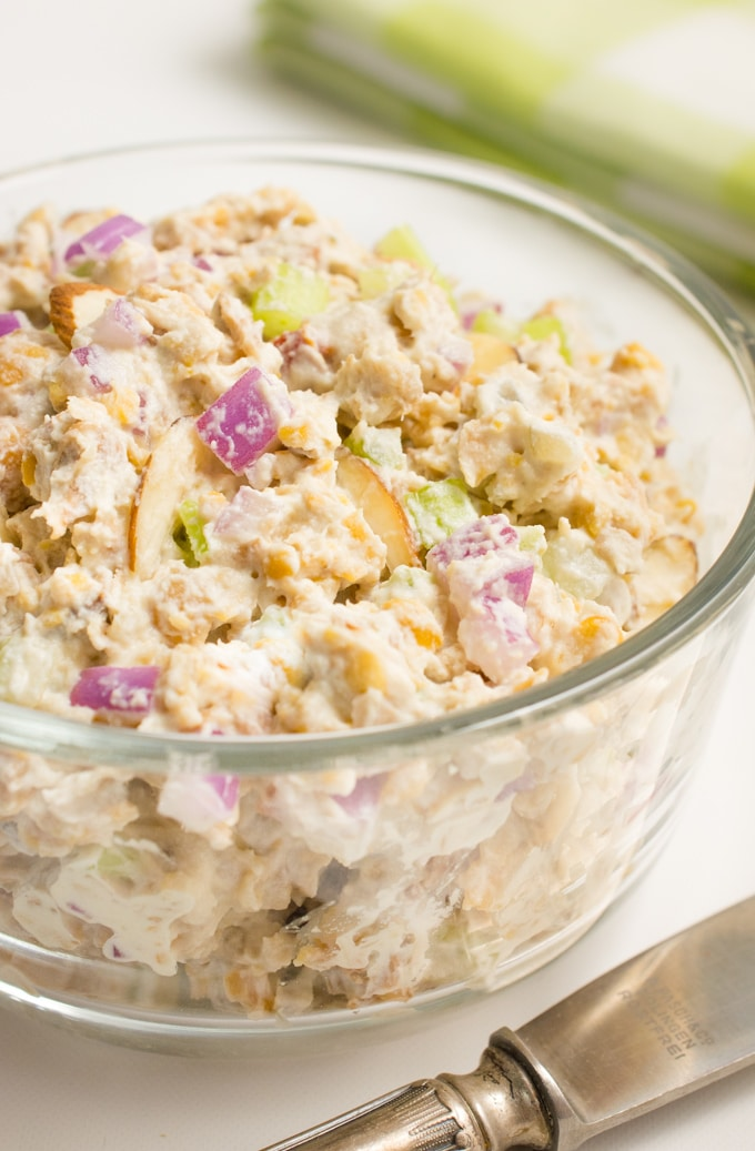 Vegan chicken salad (jackfruit, chickpeas, mayo, almond slivers, onion and celery) in a glass bowl.