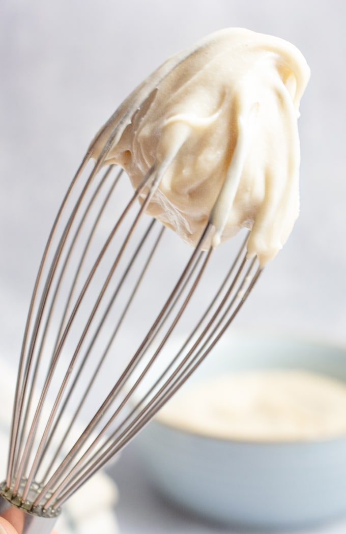 Thick, rich and creamy dairy-free frosting whipped up on on a whisk.
