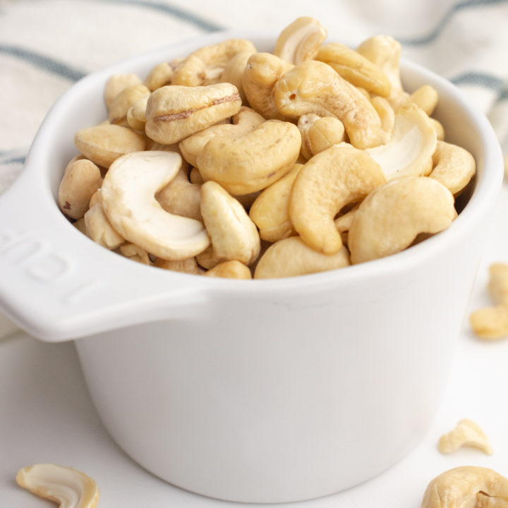 Raw cashews in a measuring cup.