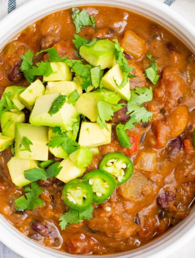 Vegan chili in a white bowl topped with diced avocado, chopped cilantro and jalapeño slices.