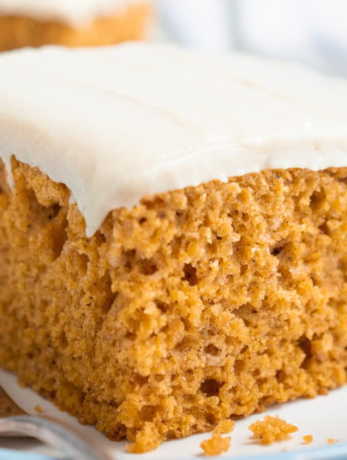 A slice of vegan pumpkin cake topped with cashew frosting.