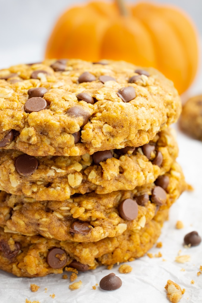 Vegan pumpkin oatmeal cookies with chocolate chips and an orange pumpkin accent