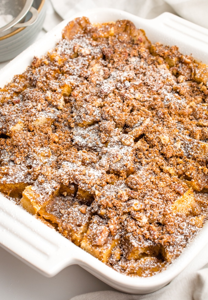 French toast casserole in a white Le Cruset topped with powdered sugar.