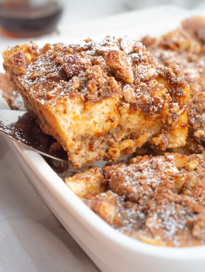 A slice of vegan french toast casserole being lifted out of the dish.