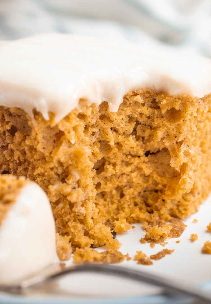 A slice of vegan pumpkin cake with a bite removed.