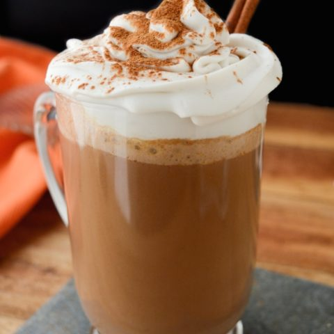Pumpkin spice hot chocolate in a glass mug topped with coconut whip and ground cinnamon.