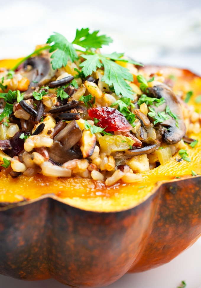 Roasted acorn squash stuffed with wild rice, mushrooms, cranberries and topped with a fresh parsley leaf.