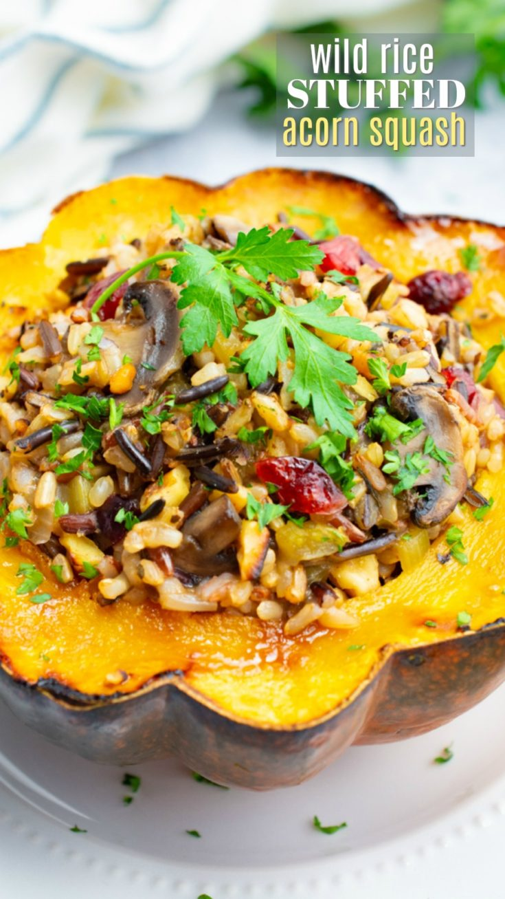 Beautifully roasted acorn squash halves are stuffed with wild rice, sautéed mushrooms, dried cranberries and seasoned with savory fall herbs. Enjoy it as a main dish at your next holiday meal or a healthy warming dinner on a cold evening. It's the perfect meatless alternative for vegans, vegetarians, and gluten-free eaters alike! #vegandinner #squash #acornsquash #vegetarian #vegan #holiday #wildrice #winter