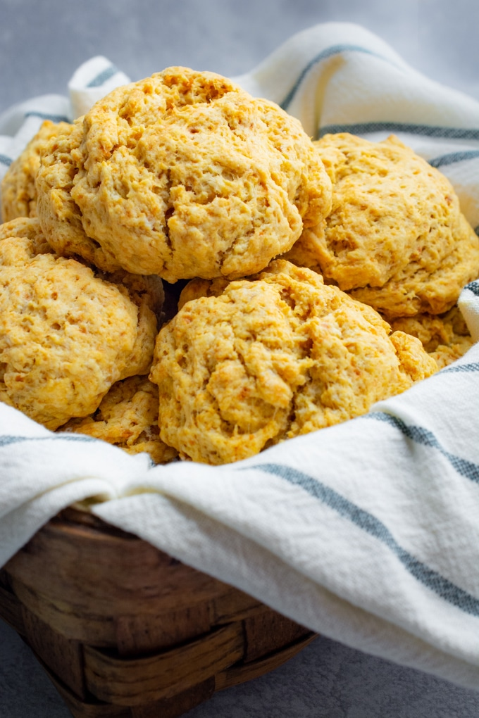 Vegan sweet potato biscuits (drop-style) in a basket with a towel.
