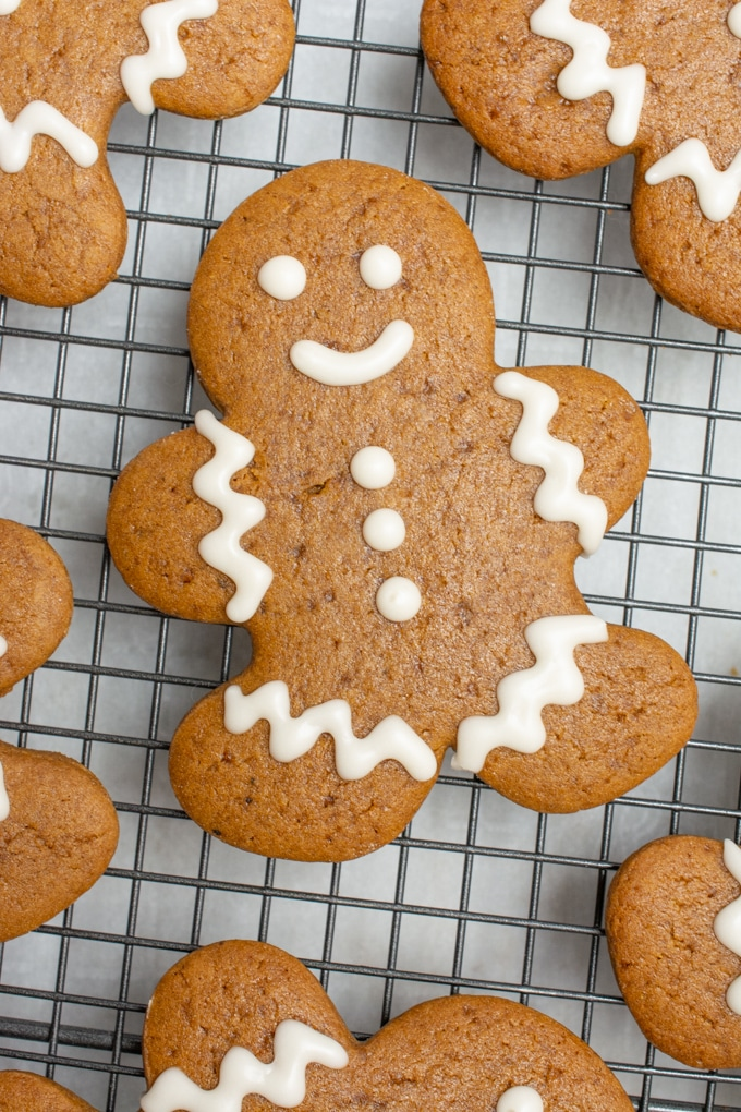 A decorated gingerbread cookie on a cooling rack.