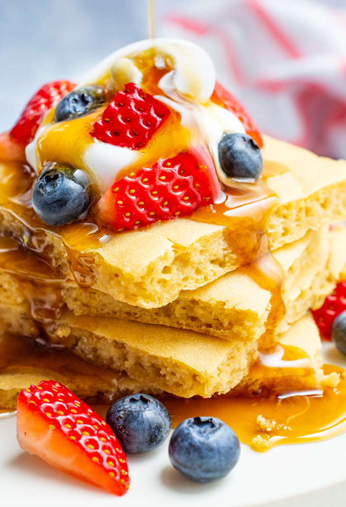 A stack of vegan pancakes topped with fruit, whip and maple syrup.