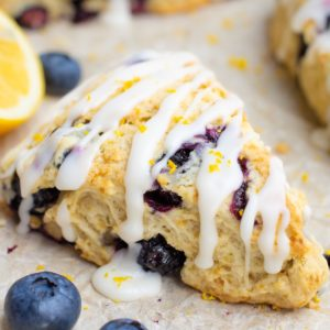 Blueberry scone with icing on parchement paper.