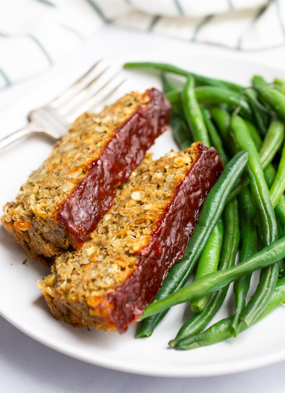 2 slices of lentil loaf topped with ketchup glaze and served with green beans.